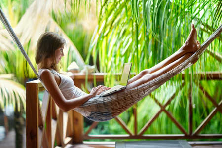 Young beautiful woman lying in a hammock with laptop in a tropical resort 版權商用圖片 - 54675124