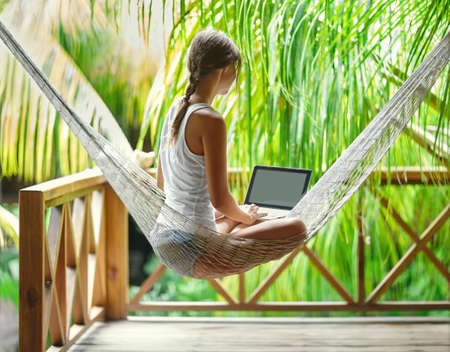 view girl: Young beautiful woman sitting in a hammock with laptop in a tropical resort. back view.