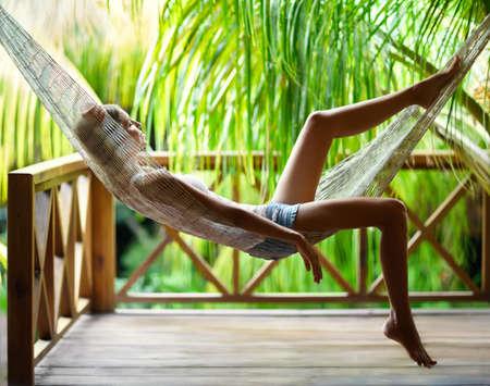 Junge schöne Frau, die in der Hängematte in einem tropischen Erholungsort sich entspannt