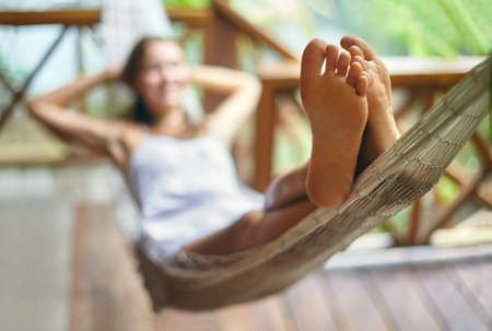 Young beautiful woman relaxing in hammock in a tropical resort. Focus on foot Banco de Imagens