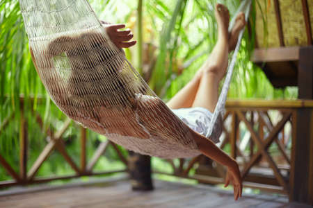 Mulher bonita nova que relaxa no hammock em uma visão resort.back tropical Imagens