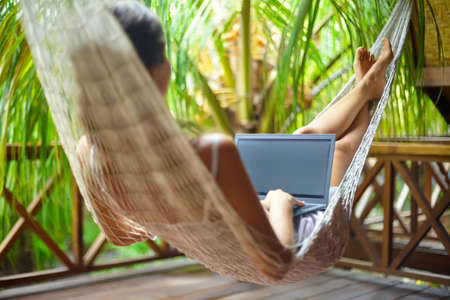 Young beautiful woman lying in a hammock with laptop in a tropical resort. back view. Foto de archivo