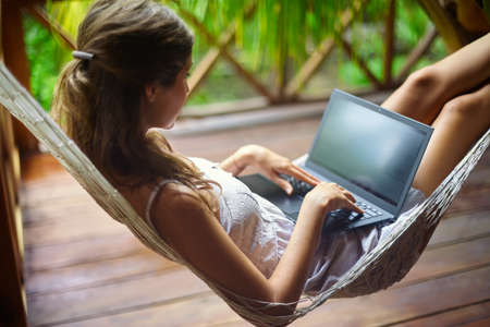 Young beautiful woman lying in a hammock with laptop in a tropical resort. back view. Stok Fotoğraf