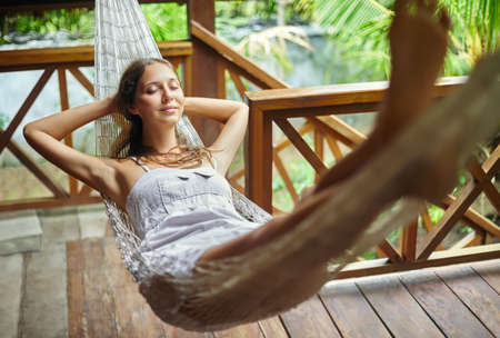Young beautiful woman relaxing in hammock in a tropical resort