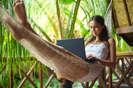 Young beautiful woman lying in a hammock with laptop in a tropical resort Reklamní fotografie - 54675382