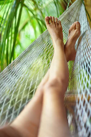 Sexy sporty woman legs in hammock.Vacation concept