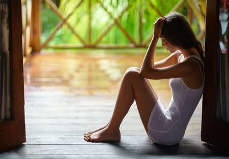 Droevige eenzame mooie vrouw zitten op de veranda tijdens de regen