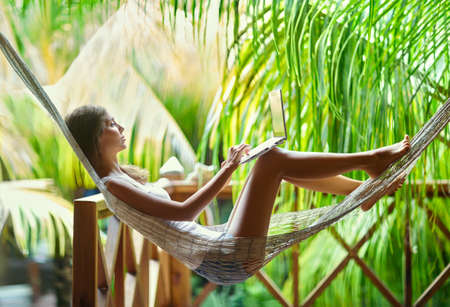 woman lying: Young beautiful woman lying in a hammock with laptop in a tropical resort