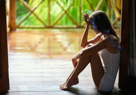 persona fumando: Sola triste bella mujer de fumar cigarrillos y sentado en el porche durante la lluvia