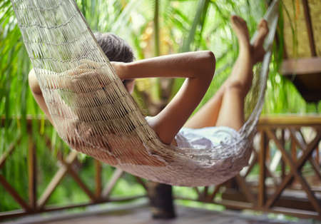 Young beautiful woman relaxing in hammock in a tropical resort.back view Stock Photo