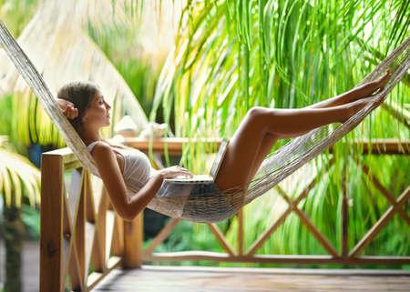 Jonge mooie vrouw liggend in een hangmat met een laptop in een tropisch resort Stockfoto