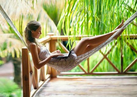 NATURE: hermosa mujer joven tumbado en una hamaca con ordenador portátil en un centro turístico tropical