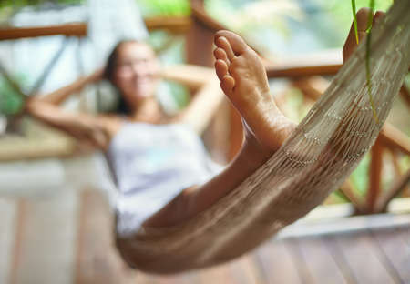 woman foot: Young beautiful woman relaxing in hammock in a tropical resort. Focus on foot Stock Photo