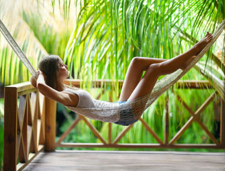 carefree: Young beautiful woman relaxing in hammock in a tropical resort