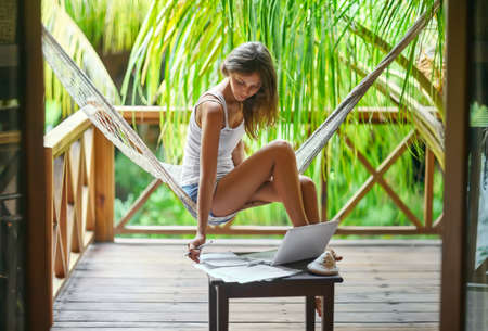 back view: Young beautiful woman sitting in a hammock with documents and laptop in a tropical resort Stock Photo