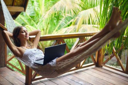 Jonge mooie vrouw ontspannen in een hangmat met een laptop in een tropisch resort. Pauze
