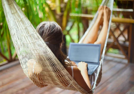 Young beautiful woman lying in a hammock with laptop in a tropical resort. back view. Banque d'images