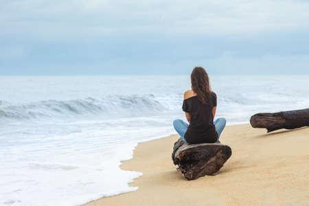 Eenzame vrouw zittend op het tropische strand bij de zee.