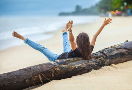 woman laying: happy freedom woman with hands up and legs up cheering on the tropical beach