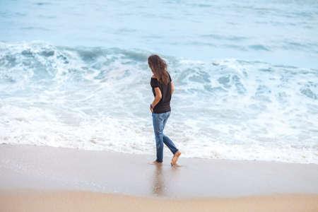 solitude: beautiful woman walking along tropical sea in storm