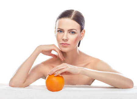 beautiful young woman with orange isolated on white background. Skin care and beauty. photo