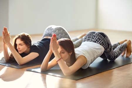asana: Two young women doing yoga asana eight limbed pose variation. Ashtanga Asana Stock Photo