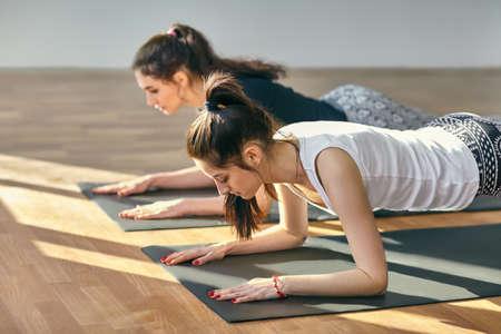 in low spirits: Two young women doing yoga asana Low Plank Pose. Ardha Phalakasana