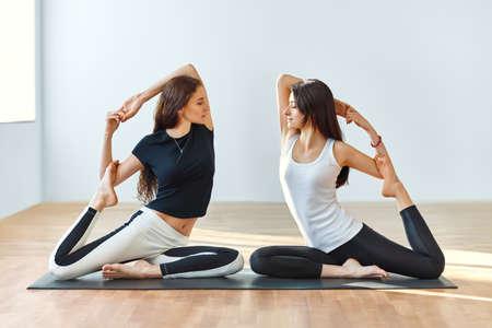 Two young women doing yoga asana Eka Pada Rajakapotasana. One legged king pigeon