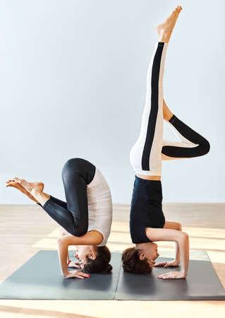shirshasana: Two young women doing yoga asana crane pose. Bakasana Stock Photo