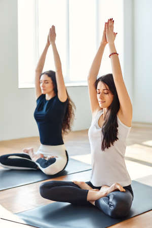 woman hands up: Two young women doing yoga asana мountain Ñ?ose. Parvatasana Stock Photo