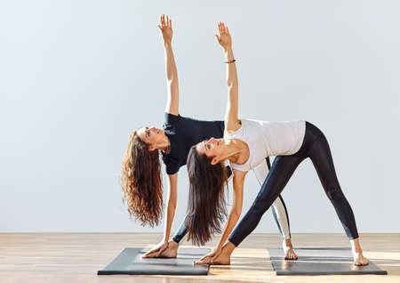 Two young women doing yoga asana extended triangle pose. Trikonasana
