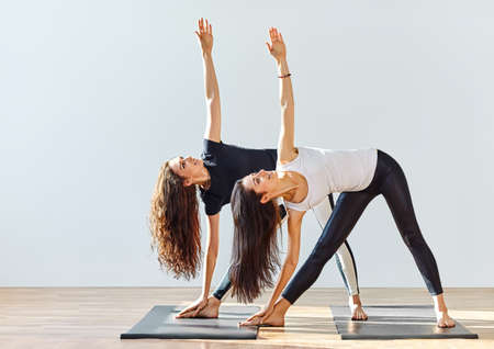 Two young women doing yoga asana extended triangle pose. Trikonasana