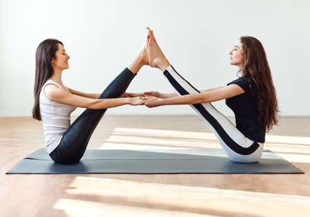 Two young women doing yoga asana buddy boat pose. Paripurna Navasana 写真素材