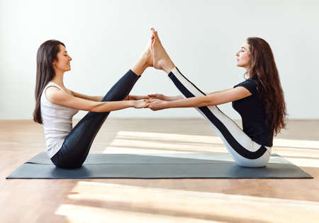 Two young women doing yoga asana buddy boat pose. Paripurna Navasana Stock fotó