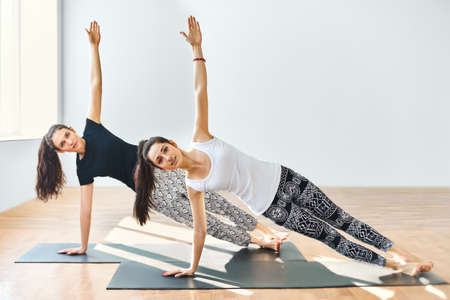 Two young women doing yoga asana side plank. Vasisthasana Standard-Bild