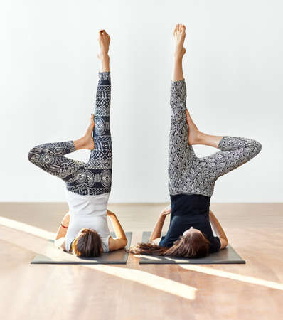 Two young women doing yoga asana supported shoulderstand. Variation of Sarvangasana
