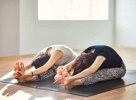 mujeres sentadas: Dos mujeres jóvenes haciendo yoga asana sentados adelante plegado. Paschimottanasana