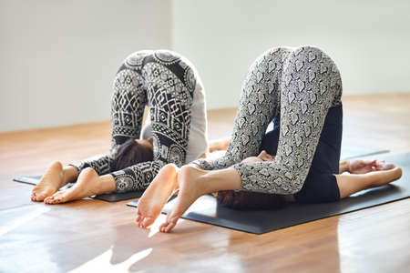 Two young women doing yoga asana easy plow pose. Purva Halasana Imagens - 60891631