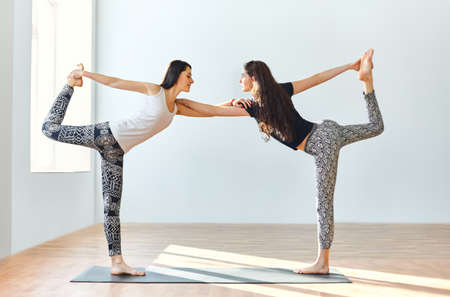Two young women doing yoga asana lord of the dance pose. Natarajasana