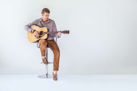 Handsome smiling guitarist play music siting on chair in studio with copy space