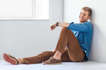 man sit: Portrait of happy handsome man sitting on th floor in studio Stock Photo