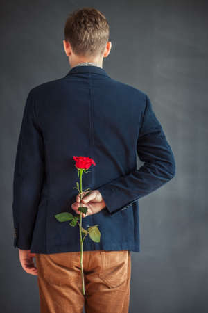gift behind back: Rear view of young man holding red rose behind his back. Surprise