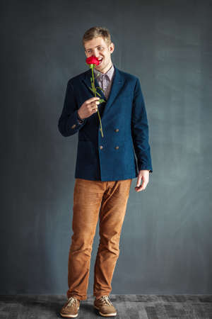 droll: Full length portrait of funny man eating red rose standing against grey wall background Stock Photo