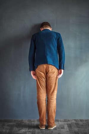 Rear view of stressed despair man punching the wall Standard-Bild