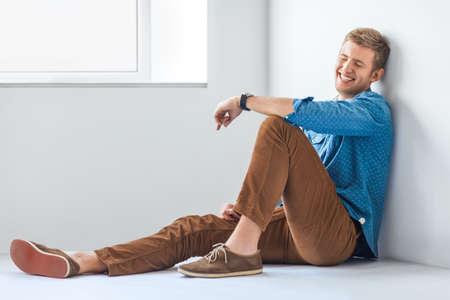 Portrait of happy handsome man sitting on th floor in studio Stock Photo