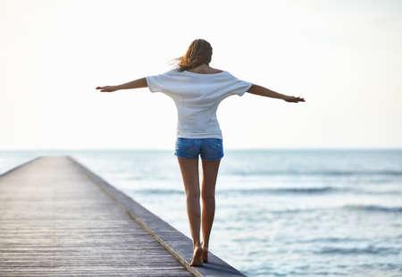 Freedom girl walking on the pier