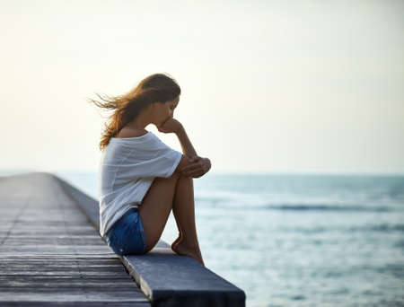 Sad lonely beautiful woman sitting on the pier with copy space