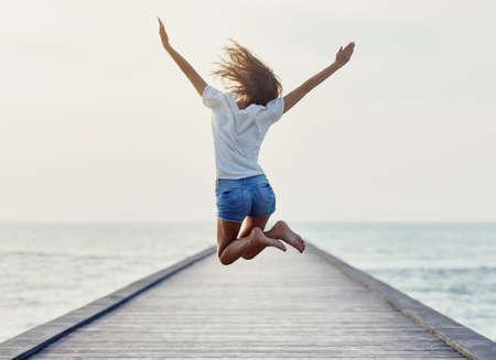 桟橋で女の子をジャンプの背面します。自由の概念 写真素材 - 61521806