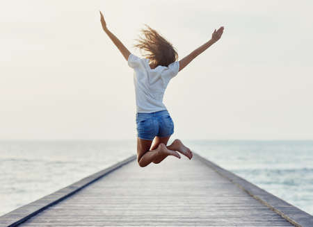 Back view of jumping girl on the pier. Freedom concept Stockfoto