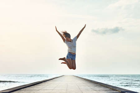 Happy jumping girl on the pier. Freedom concept Standard-Bild